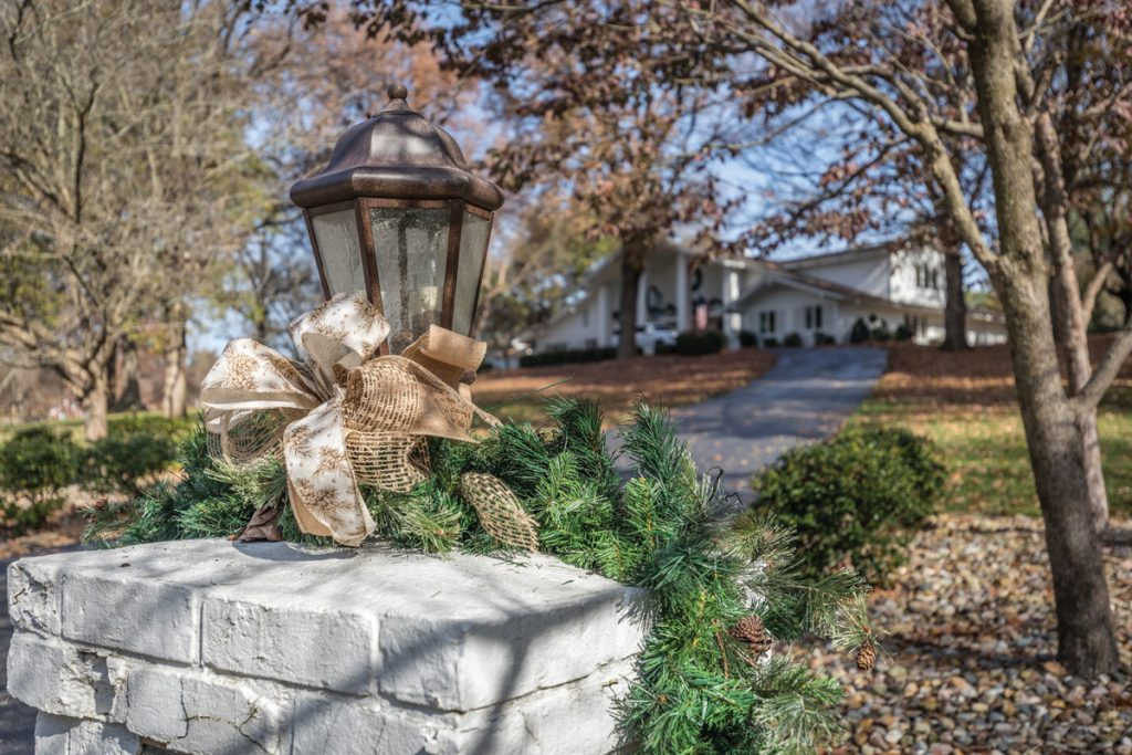 Exterior lamp decorated for Christmas with house in background
