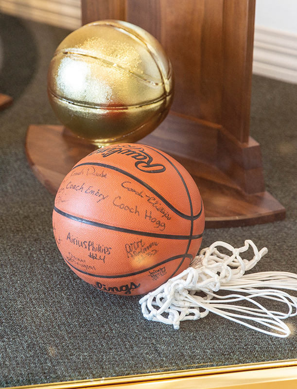 Basketball, net, and trophy in display case