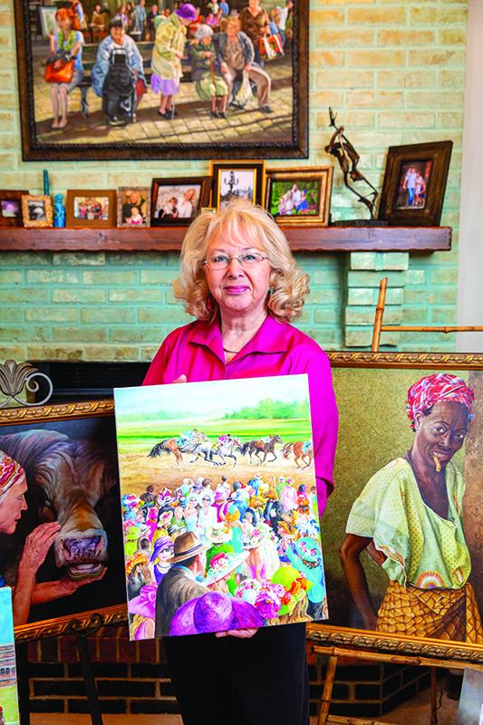 Artist Rhonda McEnroe holding a race horse painting