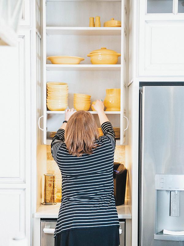 Professional organizer Sara Kathryn Fort organizing a kitchen cabinet