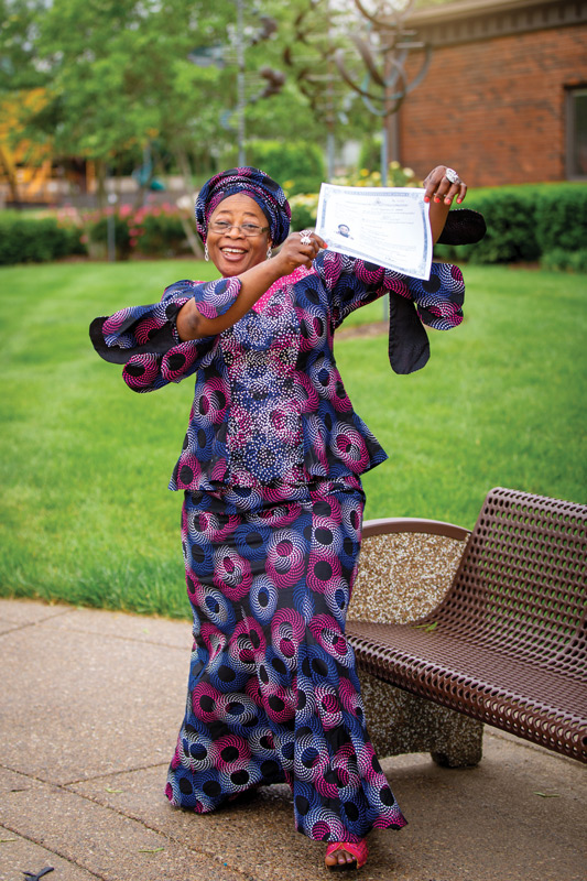 Atinuke Wilhite dances with joy as she shows off her certificate declaring permanent residency.