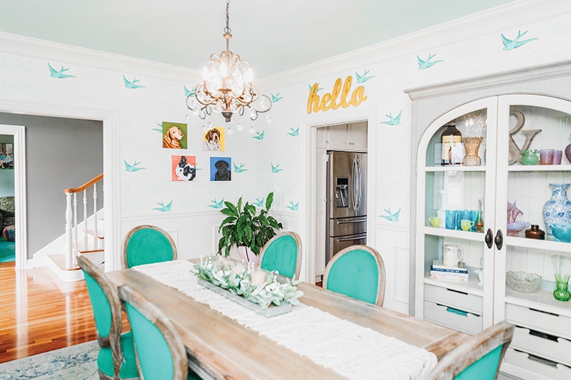 Dining room of featured home with turquoise chairs and bird wallpaper