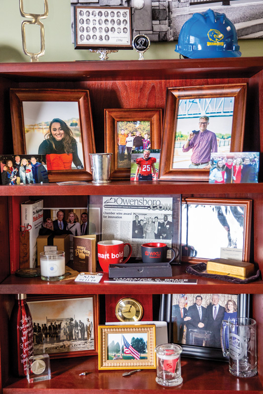 A bookcase in Brake's office is filled with family and business mementos, including graduation photos of her two children and a ceremonial brick from the Smothers Park grand re-opening.