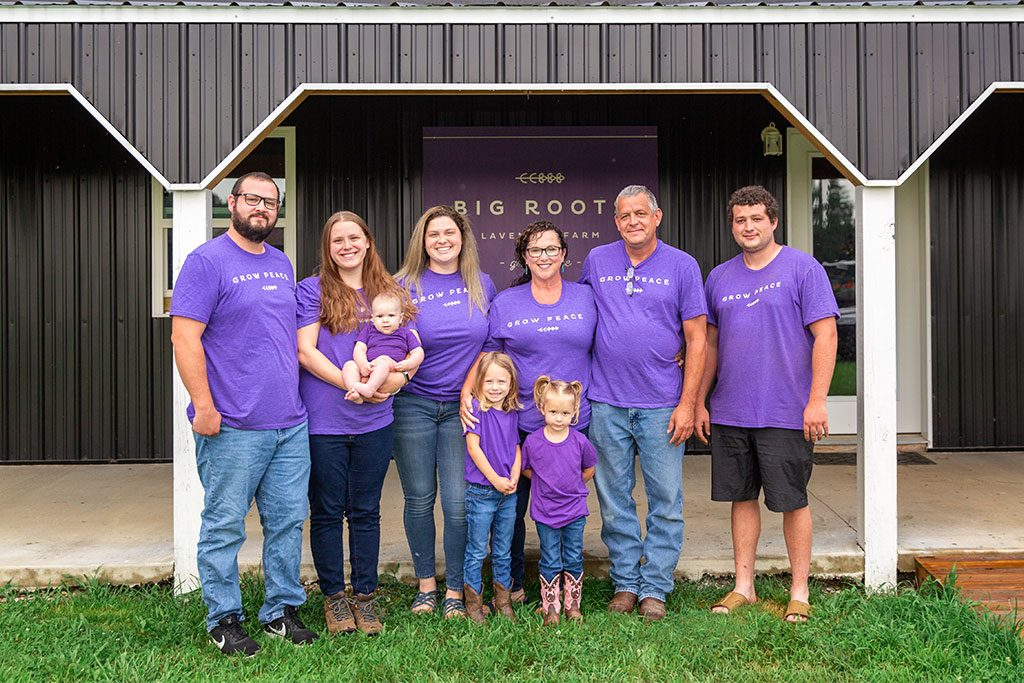 The Ramsey family smiles happily as they all wear purple 'grow peace' shirts.