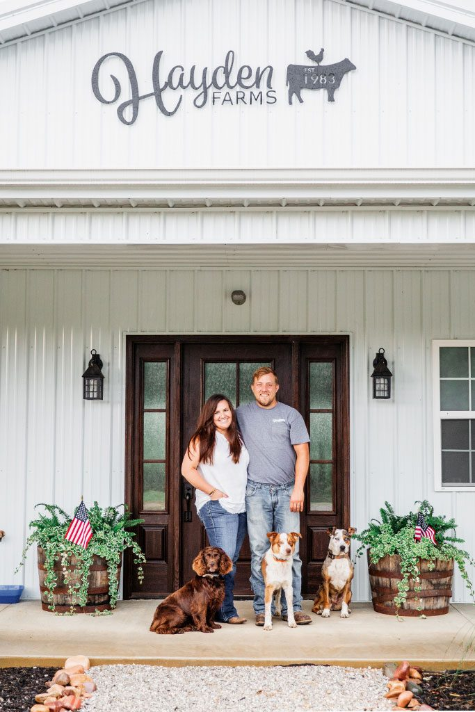 Danielle and Daniel Hayden stand smiling with their three dogs.