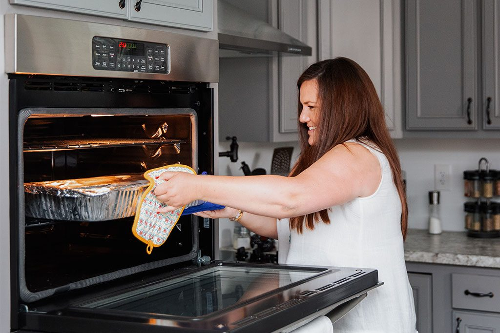 Danielle removes a large pan of food from the oven.