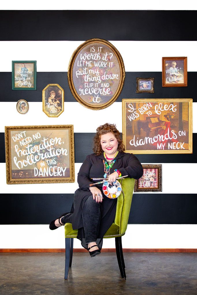 Maddox sits in a chair as her vintage paintings with bold, white, text hang on display behind her.