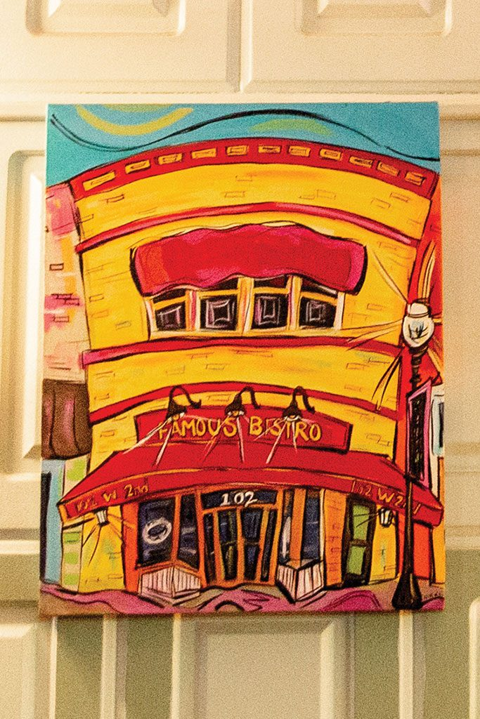 A colorful painting of the Bistro hangs near the kitchen.