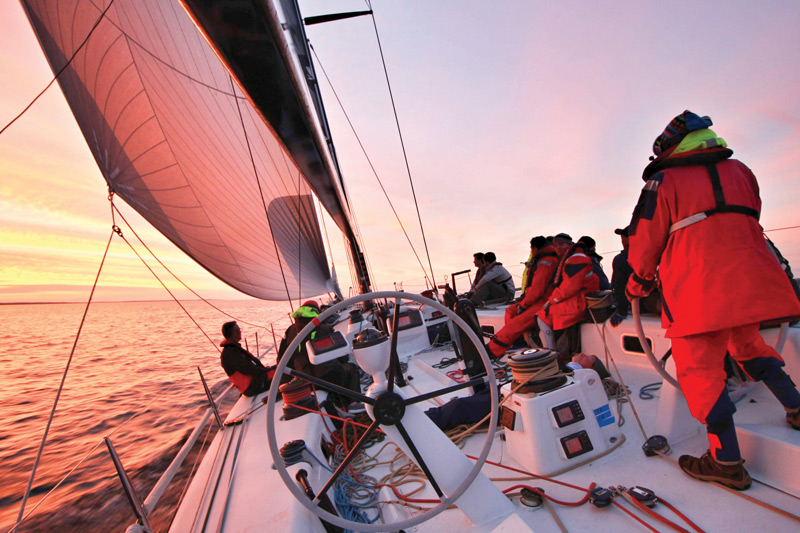 Sailing team on sailboat during sunset